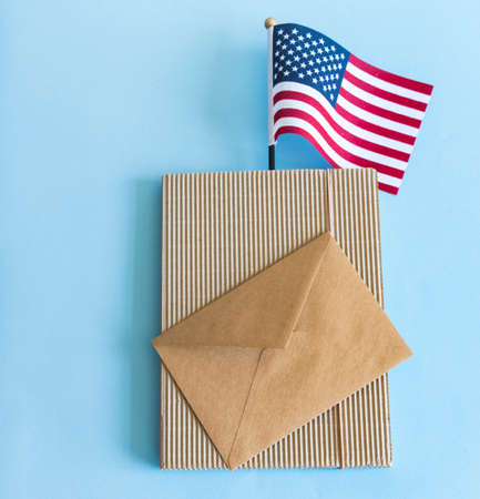 American flag and brown paper envelope on blue background. 免版税图像
