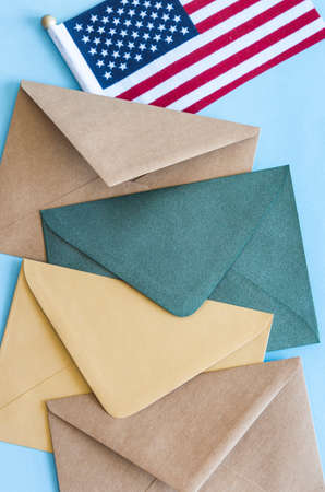 American flag and colorful envelopes on blue background. 免版税图像