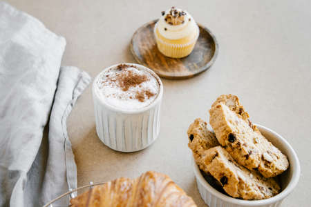 Freshly baked almond biscottis with cup of cappuccino on wooden background. Breakfast food concept.