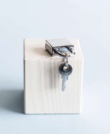 Silver shiny metal padlock with keys on wooden stand and blue background.