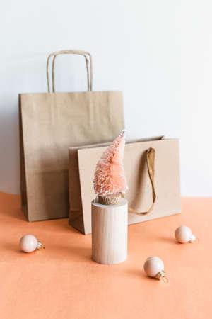 Coconut fiber orange Christmas tree on wooden stand, kraft paper gift bag on pink white background, zero waste festive concept.