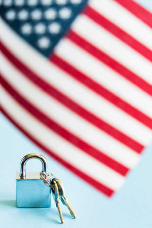 Metal silver padlock and keys with flag of the United States of America on blue background.
