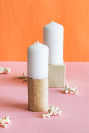 White aromatic candles on wooden stands with corals on pink and orange background.
