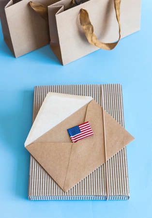Zero waste concept, kraft brown paper bags and envelope, USA flag on blue white background.