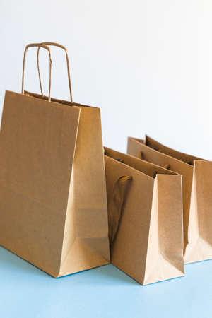 Zero waste shopping concept, kraft brown paper bags on blue white background. 免版税图像