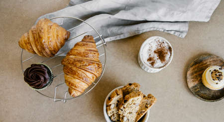 Freshly baked almond biscottis, croissants, cupcakes with cup of cappuccino background. Breakfast food concept. 免版税图像