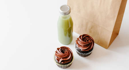 Chocolate cupcakes, green detox juice and brown paper bag on white table background. Food concept.
