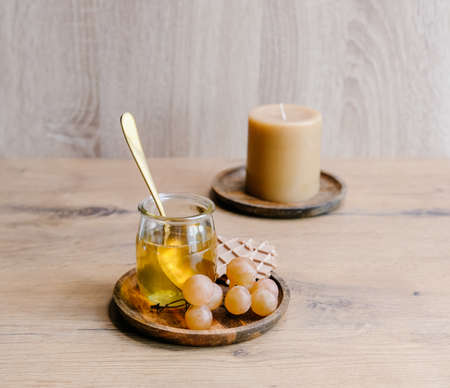 Healthy snack set with muscat grapes, honey and candles on wooden background.