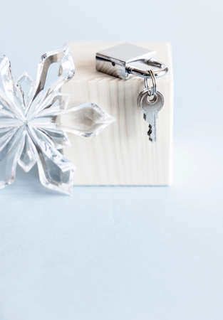 Silver shiny metal padlock with keys and glass snowflake on wooden stand and blue background.