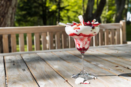Traditional summer dessert Eton mess. Mixture of meringue, whipped cream, fresh strawberries and raspberries, decorated with mint sauce on wooden table background.