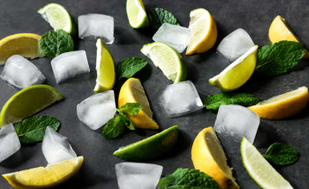 Fresh lime and lemon pieces, mint leaves and ice cubes on dark background. Summer drink or cocktail concept. 免版税图像