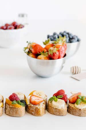 Summer fruit bruschetta with white chocolate spread, bananas, raspberries and strawberries. Breakfast snacks.