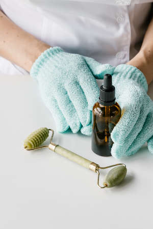 Brown plastic bottle for liquid cosmetics in womans hands in green gloves, green jade massage roller on white table. Cosmetologist holding spin care products. 免版税图像