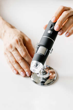 Skin microscope in womans hands. Modern cosmetology.