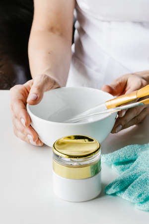 Brown plastic bottle for liquid cosmetics and wooden bowl with stone sticks for face massage in womans hands on white table. Cosmetologist holding spin care products. 免版税图像