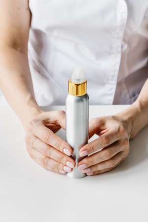 White and golden cream bottle in womans hand. Cosmetologist holding spin care product.