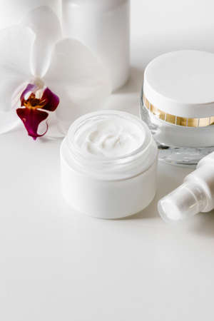 White blank cosmetic bottles, container or cream jar, serum or other cosmetic product on light background. Natural spa concept. 免版税图像