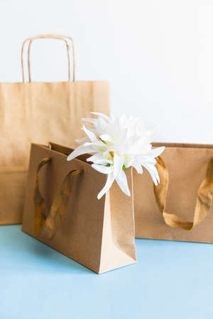 Zero waste concept, kraft brown paper bags and textile flower on light background.