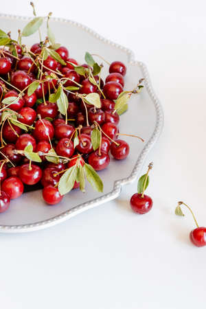 Fresh cherries with stalks and leaves on silver plate and white background.
