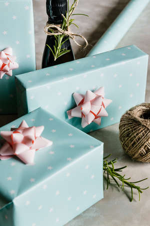 Christmas and New Year holiday background or greeting card. Pastel turquoise gift boxes with pink bows and bottle of champagne.