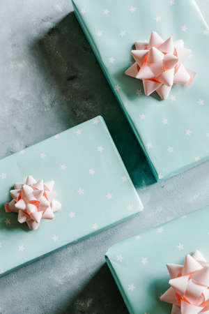 Christmas and New Year holiday background or greeting card. Pastel turquoise gift boxes with pink bows.