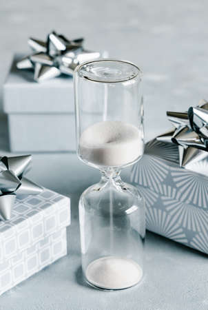 Christmas and New Year holiday background or greeting card. Gray gift boxes with silver bows and hourglass. 免版税图像