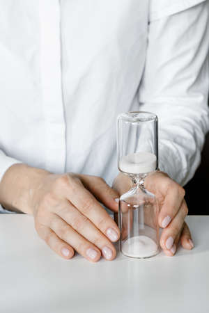 Hourglass in womans hands, sand flowing through the bulb of sandglass measuring time. White minimal concept.