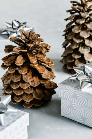Christmas and New Year holiday background or greeting card. Gray gift boxes with silver bows and pine cones.