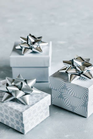 Christmas and New Year holiday monochrome background or greeting card. Gray gift boxes with silver bows.