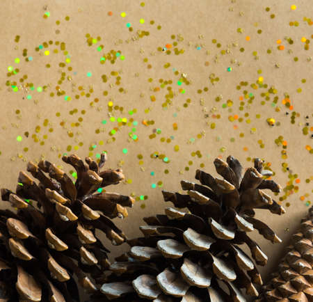 Golden Christmas glitters and pine cones on natural background. Flat lay style. Holiday classic concept.