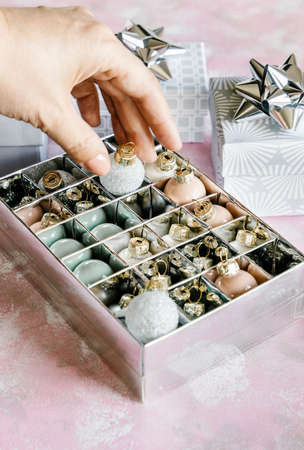 Christmas and New Year holiday background or greeting card. Mini ornaments and gray white gift boxes with silver bows.