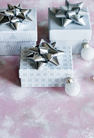 Christmas and New Year holiday background or greeting card. Gray white gift boxes with silver bows on pink.