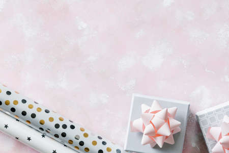 Christmas and New Year holiday background or greeting card. Gray white gift boxes with pink bows.