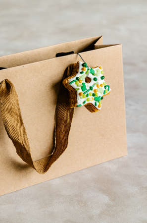 Brown paper bag decorated with gingerbread cookie, Christmas shopping concept. 免版税图像