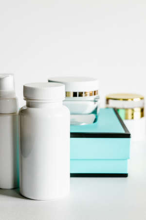 White plastic cosmetic bottles and turquoise and black gift box. 免版税图像