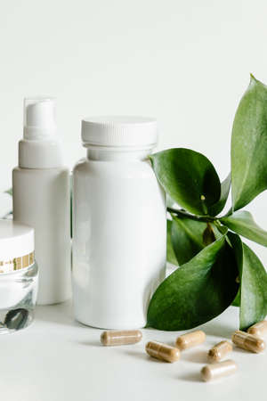 Herb capsules and white bottles, healthcare and beauty concept.