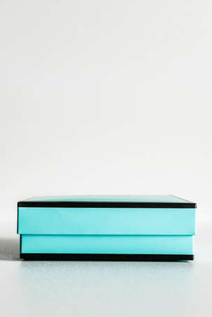 Decorative black and turquoise gift box with no bow on white background. Minimal festive concept.