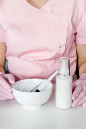 Cosmetic brushes in white bowl in womans hands. Cosmetologist in pink uniform and gloves holding skin care products. 免版税图像