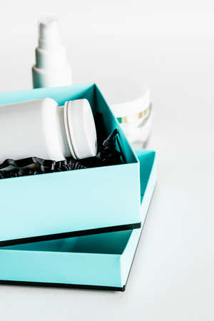 White plastic pill bottle in turquoise and black gift box.