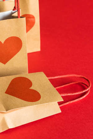 Valentines Day concept. Shopping paper bags with hearts print on red background.