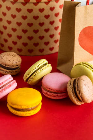 Sweet French colorful macarons on red background. Valentines Day concept.