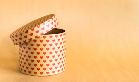 Valentines Day concept. Paper round gift box with hearts print on natural background.
