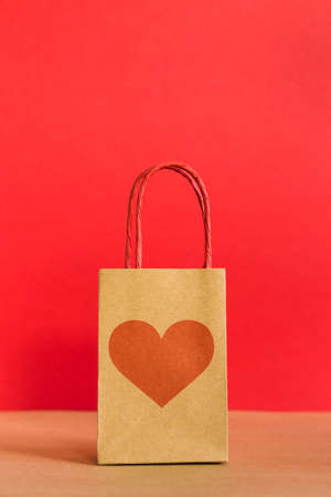 Valentines Day concept. Shopping paper bag with heart print on red background.