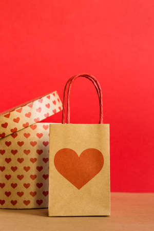Valentines Day concept. Shopping paper bags and round gift box with hearts print on red background. 免版税图像