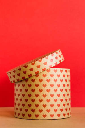 Valentines Day concept. Paper round gift box with hearts print on red background.