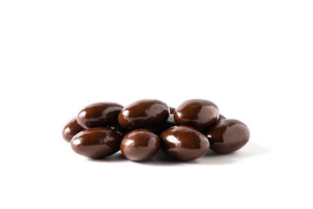 Dark chocolate covered almonds on white background, isolated. 免版税图像