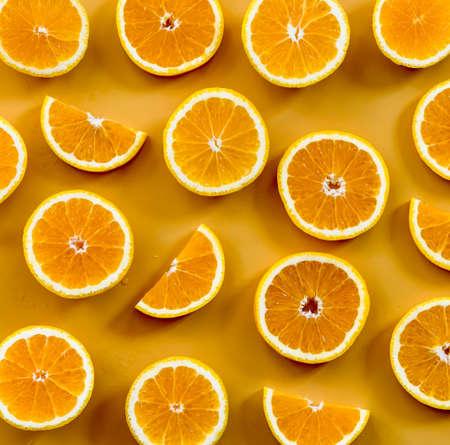 Fresh oranges sliced on orange background.