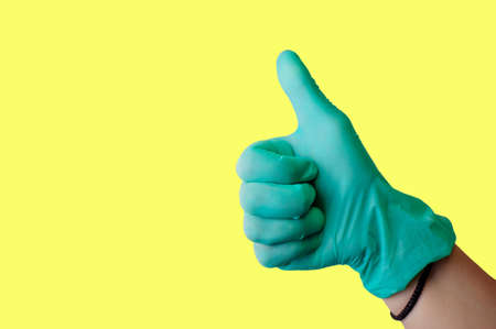 Female hand in blue latex glove makes thumbs up like gesture isolate on a light yellow background. Medical health concept. Copy space