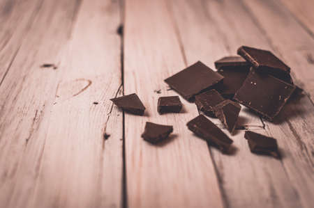 dark chocolate without sugar and gluten free for diabetics and allergics. Black chocolate broken into pieces lies on a white table in a rustic style. Dark toning and vignette. Фото со стока