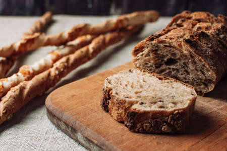 dark yeast-free buckwheat bread in a cut lies on a cutting wooden board on a wooden table, next to it is Italian grissini on a linen tablecloth in a rustic style. Breakfast cooking concept.